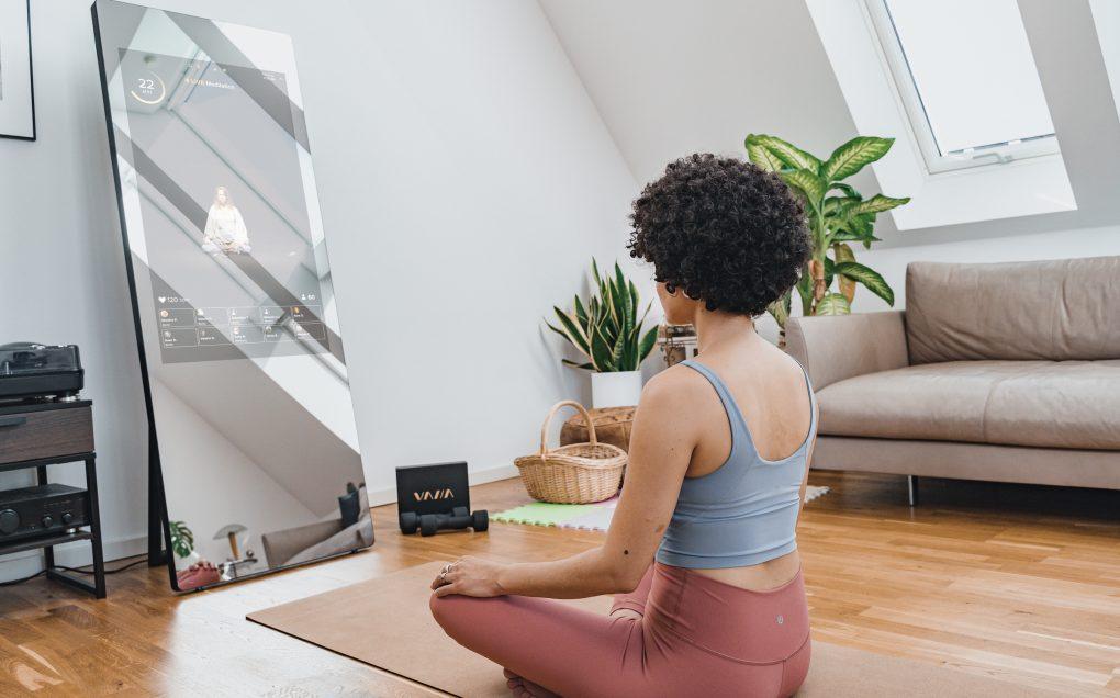 woman meditating infant of the VAHA fitness mirror
