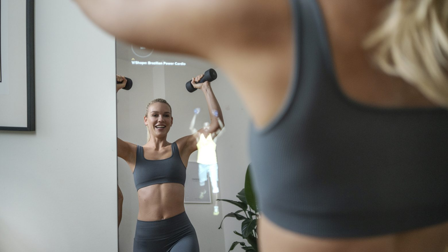 woman working out infant of the VAHA fitness mirror