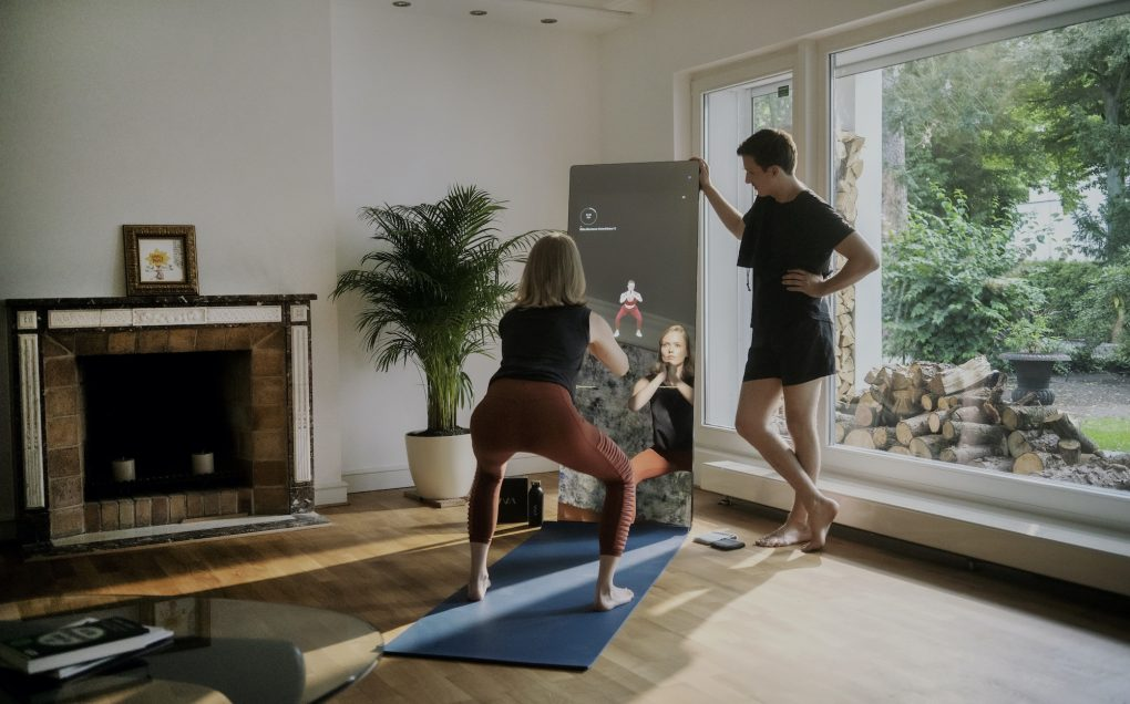 Couple training in front of the VAHA fitness mirror