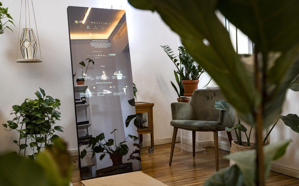 VAHA fitness mirror in a green livingroom.