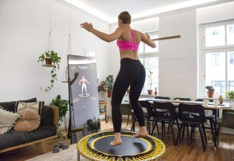 Frau trainiert mit dem VAHA Fitnessspiegel und dem bellicon Trampolin